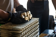 An Airman from the 57th Equipment Maintenance Squadron grabs ten pieces of 20 millimeter ammunition during Green Flag West, June 11, 2018, at Nellis Air Force Base, Nevada. The 366th EMS augmented 57th EMS Airmen during Green Flag. This exercise enhanced readiness by providing Close Air Support training over the National Training Center, Fort Irwin, California. (U.S. Air Force photo by Airman 1st Class JaNae Capuno)