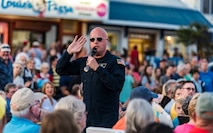 Senior Master Sgt. Ryan Carson, Max Impact superintendent and vocalist, walks in the audience during a performance June 16, 2018, at Rehoboth Beach, Del. Hundreds of beachgoers watched Max Impact perform for more than an hour during the Rehoboth Beach Bandstand Summer Concert Series. Max Impact, the premier rock band of the U.S. Air Force, is stationed at Joint Base Anacostia-Bolling in Washington, D.C. (U.S. Air Force photo by Roland Balik)