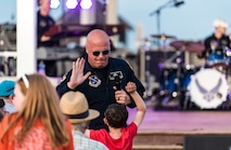 Senior Master Sgt. Ryan Carson, Max Impact superintendent and vocalist, prepares to give a high five to a young spectator during the band's performance June 16, 2018, on the bandstand at Rehoboth Beach, Del. Max Impact performed 20 songs for hundreds of beachgoers during the free, public concert. Max Impact, the premier rock band of the U.S. Air Force, is stationed at Joint Base Anacostia-Bolling in Washington, D.C. (U.S. Air Force photo by Roland Balik)