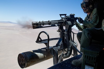 """Staff Sgt. Andrew Weanie, a helicopter crew chief with Marine Light Attack Helicopter Squadron 775, Marine Aircraft Group 41, 4th Marine Aircraft Wing, fires a GAU-17 while conducting a close air support mission during Integrated Training Exercise 4-18 at Marine Corps Air Ground Combat Center Twentynine Palms, Calif., June 18, 2018. HMLA-775, also known as the """"Coyotes"""", provided air combat element support to Marine Air Ground Task Force 23 during ITX 4-18. (U.S. Marine Corps photo by Lance Cpl. Samantha Schwoch/released)"""