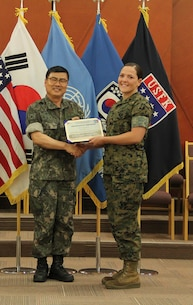 USAG CAMP HUMPHREYS, Korea – Command Sgt. Maj. Joo Sik Kim, Combined Forces Command, Ground Component Command sergeant major (left), presents a certificate of completion to Staff Sgt. Amanda D. Vincent, U.S. Marine Corps Forces Korea adjutant chief, during the U.S. Forces Korea Security Cooperation Leader Development Program graduation ceremony here, June 8. The program fostered understanding of U.S.-ROK support for security cooperation, combined capability development, and development of partner capacity. (Official U.S. Marine Corps photo by Sgt. Nathaniel Hanscom/Released)