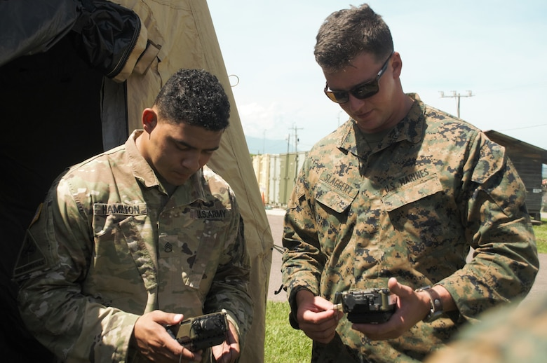 U.S. Army Staff Sgt.Tyrone Hamilton, left, the forward support noncommissioned officer in charge with Joint Task Force - Bravo's 1st Battalion, 228th Aviation Regiment, and U.S. Marine Cpl. Tyler Slaggert, a field radio operator with Special Purpose Marine Air-Ground Task Force - Southern Command, link their communications equipment together to secure reliable voice communication during a communications exercise aboard Soto Cano Air Base, Honduras, to prepare for future joint-level operations, June 19, 2018. The Marines and sailors of SPMAGTF-SC are conducting security cooperation training and engineering projects alongside partner nation military forces in Central and South America. The unit is also on standby to provide humanitarian assistance and disaster relief in the event of a hurricane or other emergency in the region.