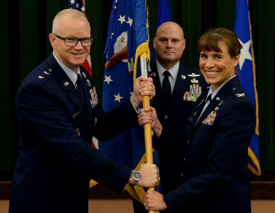 Maj. Gen. Chris Weggeman, Air Forces Cyber commander, presents the 67th Cyberspace Wing guidon to Col. Melissa Cunningham, 67th CW commander, during the wing's change of command ceremony at Joint Base San Antonio-Lackland, Texas, June 20, 2018. Col. Bradley Pyburn relinquished command of the wing to Cunningham. (U.S. Air Force photo by Tech. Sgt. R.J. Biermann)