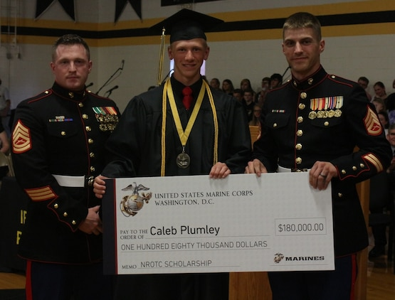 IRON MOUNTAIN, Mich. -- Gunnery Sgt. Pete Vargo and Staff Sgt. Eric Fritz, Recruiting Substation Green Bay Recruiters, presented Caleb Plumley with the Naval Reserve Officers Training Corps Marine scholarship at graduation from Iron Mountain High School. NROTC trains future leaders in the Navy and Marine Corps while they attend college.  Plumley plans to become a Marine Corps officer after graduation from the University of Michigan. (U.S. Marine Corps photo by Cpl. Emma S. Norris)