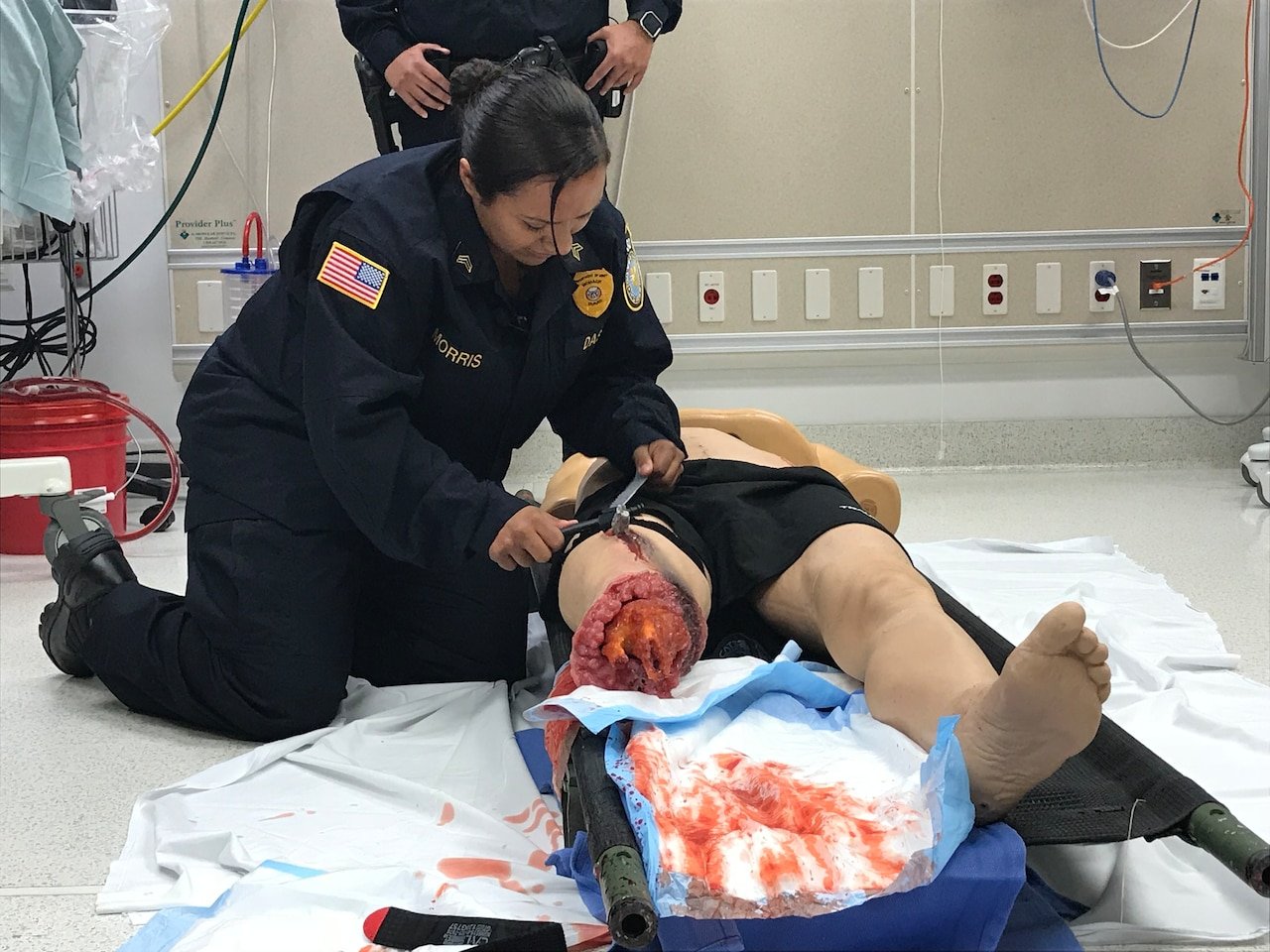 A security officer applies a tourniquet on a simulated casualty.