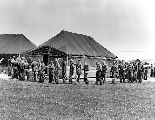 Airmen wait in line for a mean during summer training encampment June 16-17, 1956 at Camp Williams (now Volk Field), Wis.