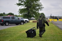 Tech. Sgt. Charles Piccolomini, 166th Civil Engineer Squadron explosive ordnance disposal technician carries his gear toward the simulated suspicious package during a suspicious package training event at New Castle Air National Guard Base, Del., June 21, 2018. The training provided an opportunity to train and execute emergency response procedures in the event a suspicious package were reported on base. (U.S. Air National Guard photo by Senior Airman Katherine Miller)