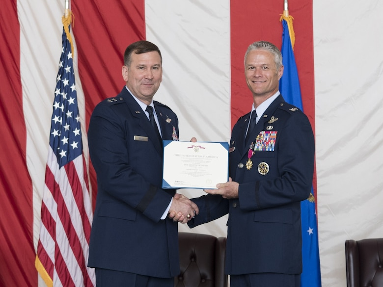 Maj. Gen. Christopher Bence, U.S. Air Force Expeditionary Center commander, presents Col. Charles Henderson with the Legion of Merit during the change of command ceremony where Henderson relinquished command of the 621 CRW to Marshall here June 21.