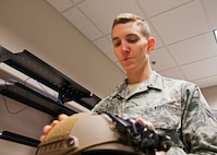Airman 1st Class Stephen Lowmiller, a 919th Special Operations Support Squadron aircrew flight equipment journeyman, inspects an Ops-Core helmet in his workcenter at Duke Field, Fla. recently.