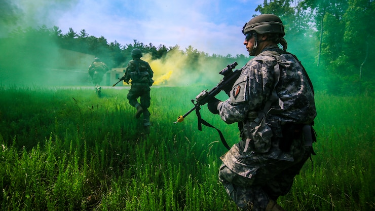 A soldier in the background runs across a field toward green and yellow smoke, as another one kneels in the foreground.