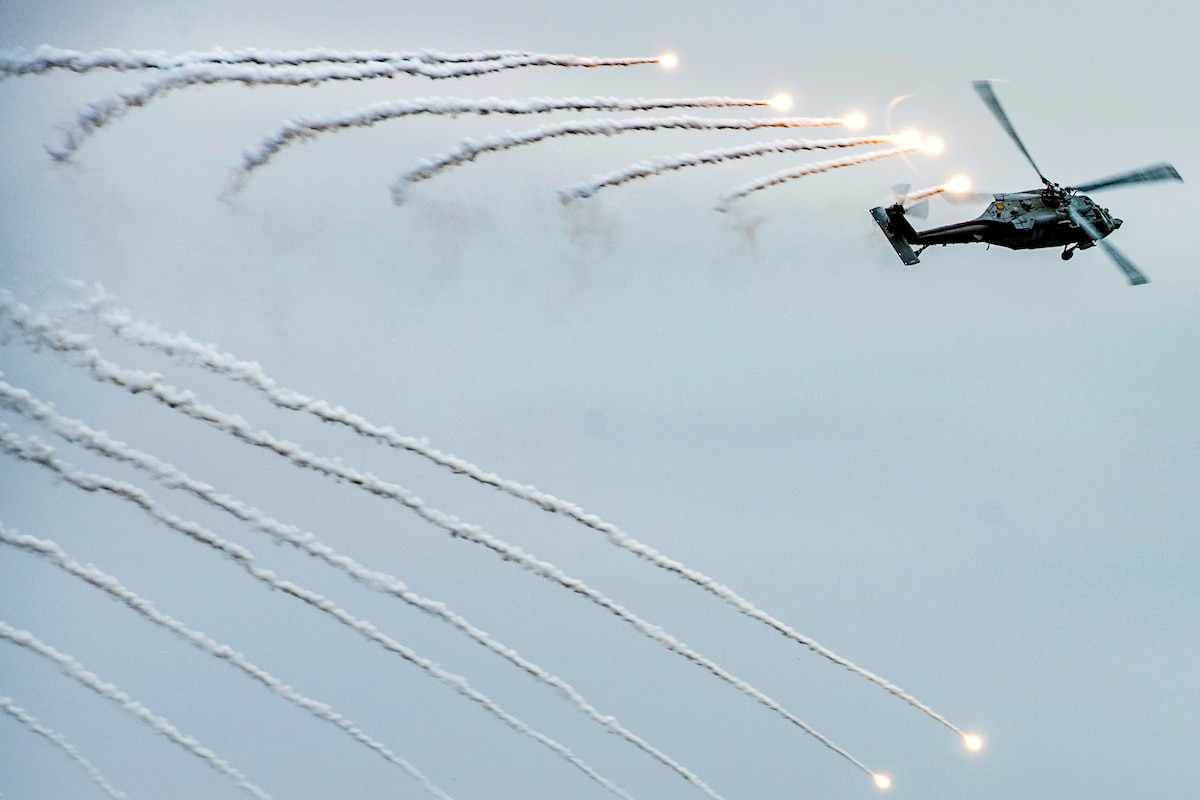 Flares burst in a linear pattern in the sky behind a helicopter firing them.