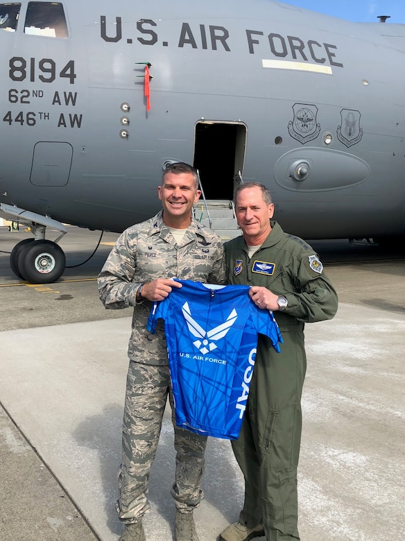 During a recent visit to McChord Field, Col. Sean P. Pierce, 446th Airlift Wing commander, pauses for a photo with Air Force Chief of Staff Gen. David L. Goldfein holding the U.S. Air Force triathlon jersey. Pierce competed in the Armed Forces Triathlon Championship and the Air Force team won a silver medal. (Courtesy photo)
