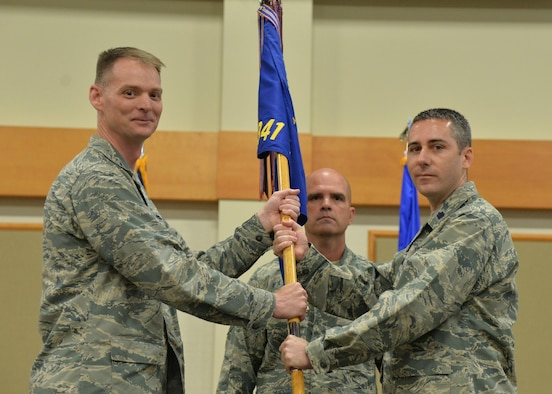 Lt. Col. Scott Schlegelmilch, right, accepts command of the 341st Missile Maintenance Squadron from Col. David Miller, 341st Maintenance Group commander, during a change of command ceremony June 21, 2018, at the Grizzly Bend at Malmstrom Air Force Base, Mont. Guidon bearer Senior Master Sgt. Robert Taylor, 341st MMXS first sergeant, looks on. (U.S. Air Force photo by Airman 1st Class Jacob M. Thompson)