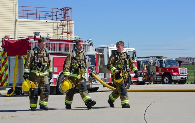 Rapid City Fire Department cadets walk across the fire training area during a training exercise at Ellsworth Air Force Base, S.D., June 21, 2018. During the exercise, cadets and firefighters put out 15 controlled fires burning at 700 degrees Fahrenheit. (U.S. Air Force photo by Senior Airman Randahl J. Jenson)