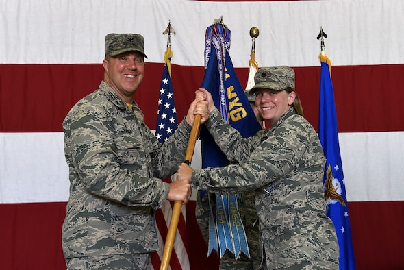 U.S. Air Force Maj. Kristen Torma receives the 51st Maintenance Squadron (MXS) guidon from Col. Michael Hammond, 51st Maintenance Group commander, during a change of command ceremony at Osan Air Base, Republic of Korea, June 21, 2018. Prior to taking leadership of 51st MXS, Torma served as commander of the 20th Aircraft Maintenance Squadron at Shaw Air Force Base, South Carolina. (U.S. Air Force photo by Senior Airman Kelsey Tucker)
