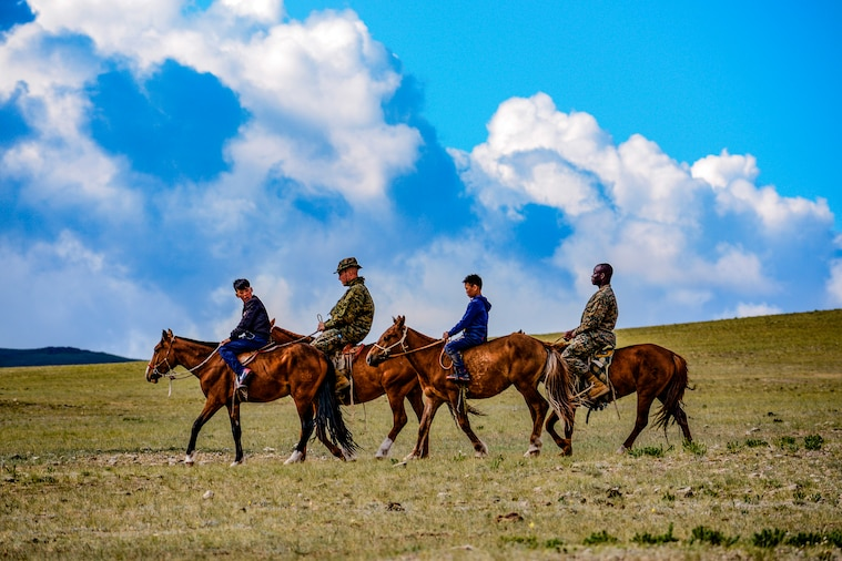 Two Marines and two youths ride horses in a line.