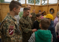U.S. Marines with 2nd Civil Affairs Group, Latvian Zemessardze (national guardsmen) and children from Priedites Orphanage intermingle at a local pottery art house in Daugavpils, Latvia, June 5, 2018, during a community event as part of Exercise Saber Strike 18. The Marines and Latvian Zemessardze, with the help of a nonprofit charity organization Spirit of America, visited the children of the Priedites Orphanage and treated them to a day full of activities including a trip to a local pottery art house and an outdoor playground obstacle course. Spirit of America is a non-profit organization that works alongside forward-deployed troops and diplomats serving overseas to identify critical needs and provide private-sector resources and know-how in support of their missions to increase their safety and success.(U.S. Marine Corps photo by Sgt. Adwin Esters/Released)