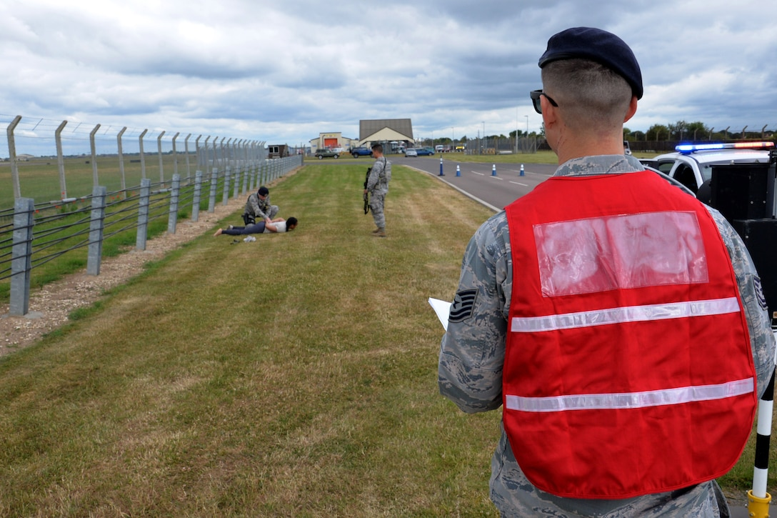 A member of the 100th Air Refueling Wing inspection team observes as U.S. Airmen from the 100th Security Forces Squadron search a simulated suspect during an exercise at RAF Mildenhall, England, June 20, 2018. Such exercises are regularly scheduled to test responsiveness and readiness of base personnel. (U.S. Air Force photo by Tech. Sgt. David Dobrydney)