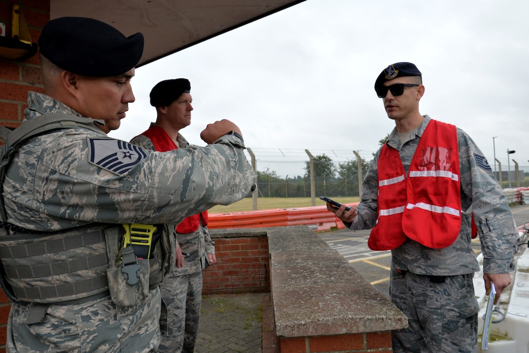 U.S. Air Force Master Sgt. Brad Miller, 100th Security Forces Squadron flight chief, speaks with Master Sgt. Matthew Kline and Tech. Sgt. Anthony Laspino, 100th Security Forces Squadron inspection team members, during an exercise at RAF Mildenhall, England, June 20, 2018. Such exercises are regularly scheduled to test responsiveness and readiness of base personnel. (U.S. Air Force photo by Tech. Sgt. David Dobrydney)