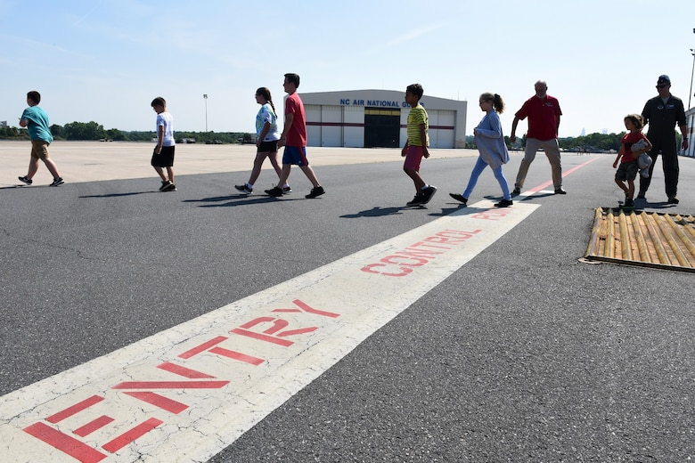 Children of North Carolina (NC) Air National Guardsmen are escorted across the entry point of a flight line before touring a C-17 Globemaster III aircraft held at the NC Air National Guard Base, Charlotte-Douglas International Airport, June 18, 2018. The children are part of the annual Department of Defense STARBASE summer camp program and learn various applications of science, technology, engineering, and math.