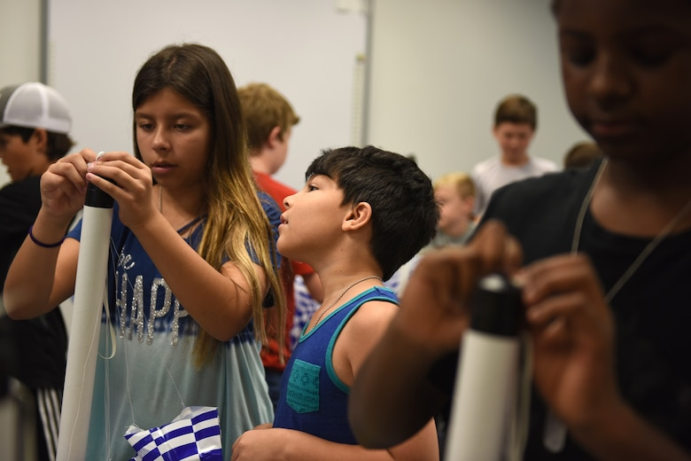 Valentina Olaya (left), helps Josue Samudil (right), son of U.S. Air Force Staff Sgt. Brittany Coleman, military pay technician with the 145th Comptroller Flight, with building his model rocket during a lesson held at the North Carolina Air National Guard Base, Charlotte-Douglas International Airport, June 18, 2018. The children are part of the annual Department of Defense STARBASE summer camp program and learn various applications of science, technology, engineering, and math.