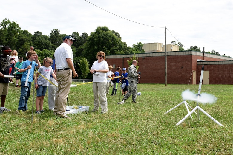 Parents, campers, and teachers watch as model rockets launch near Reid Park Academy Charlotte, N.C., June 21, 2018. The campers and teachers are part of the annual Department of Defense STARBASE summer camp program with the North Carolina Air National Guard and they learn various applications of science, technology, engineering, and math.