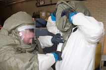 U.S. Air Force Senior Airman William Davis, 55th Medical Support Squadron pharmacy technician and member of the In-Place Patient Decontamination (IPPD) Team, checks the disposable toxic agent protective suit on a teammate during a product evaluation at the Ehrling Bergquist Clinic June 7, 2018, at Offutt Air Force Base, Nebraska. Members of the IPPD Team simulated working in a contaminated environment while testing three new patient decontamination systems. (U.S. Air Force photo by Paul Shirk)
