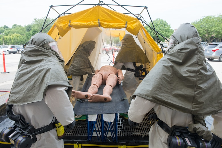 Members of the In-Place Patient Decontamination Team carry a mannequin into a patient decontamination system during a product evaluation at the Ehrling Bergquist Clinic June 7, 2018, at Offutt Air Force Base, Nebraska. The system is used to wash dangerous materials off of patients before they enter a military treatment facility. (U.S. Air Force photo by Paul Shirk)