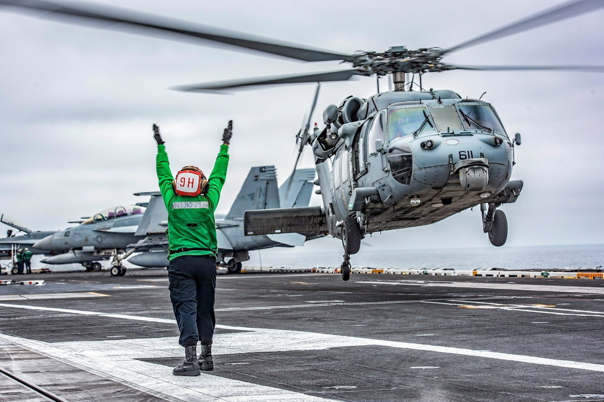 A sailor in green, shown from behind, extends her arms upward as a helicopter takes off from a ship's flight deck.
