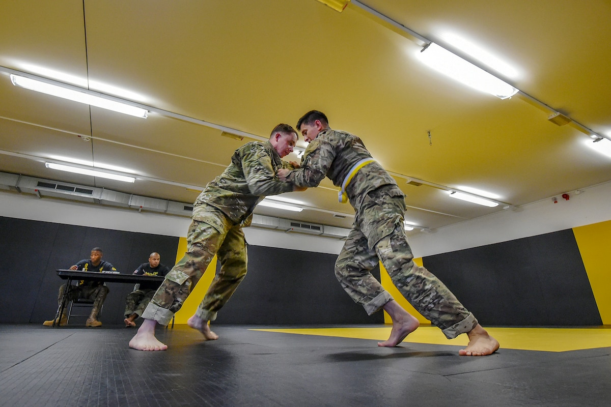 Soldiers grapple in a gym with yellow walls.