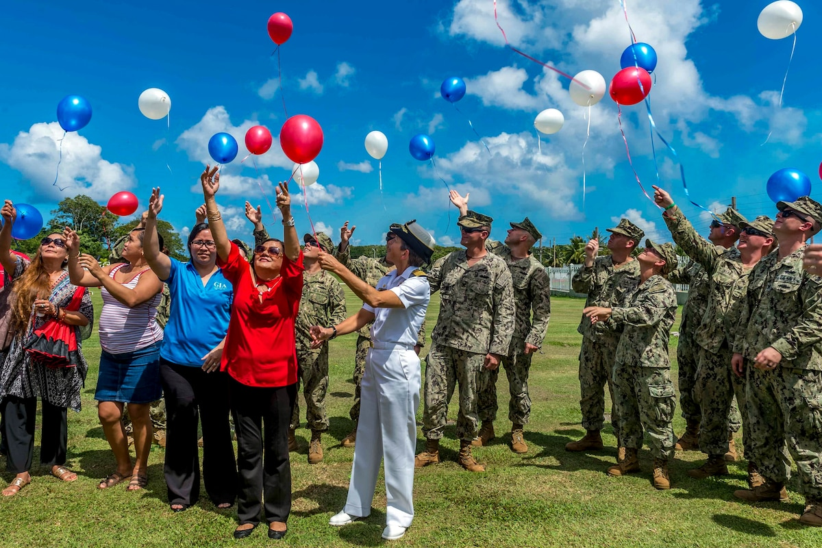 Civilians and service members release red, white and blue balloons in a field outside.