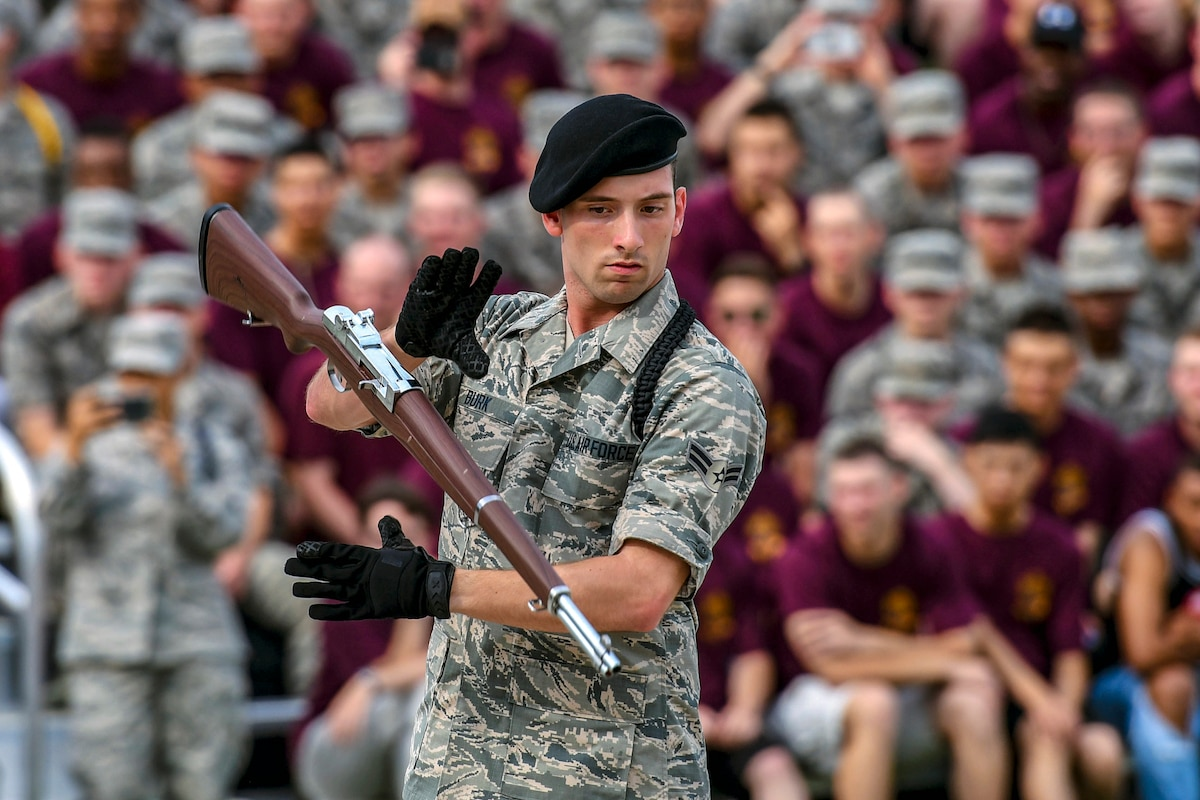 An airman in black gloves performs a drill routine with a rifle as a crowd watches.