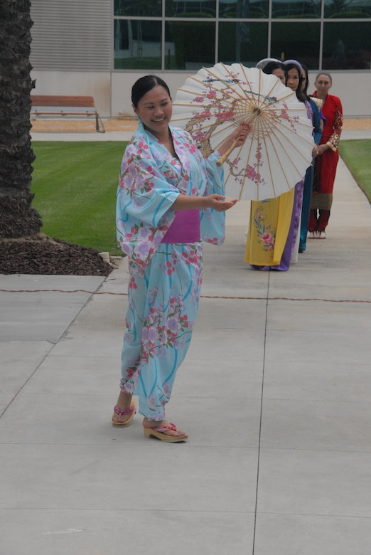 Tech. Sgt. Kristin Rosales, noncommissioned officer in charge of Medical Materiel at the 61st Medical Squadron, performs a traditional dance wearing a turquoise floral Japanese kimono.