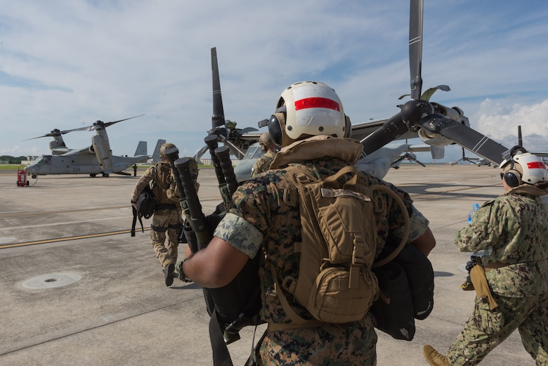 Members of the U.S. Air Force, Navy and Marines, board an MV-22 Osprey, June 6, 2018, at Marine Corps Air Station, Okinawa, Japan during an exercise. The Air Force performs joint medical exercises with other U.S. forces regularly in Okinawa to better prepare service members for real world emergencies. (U.S. Air Force photo illustration by Josh Mahler)