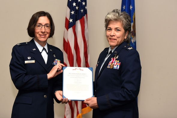 U.S. Air Force Col. Janet Urbanski, 17th Medical Group commander, presents a meritorious service certificate to Col. Kari Stone, 17th Medical Operation Squadron outgoing commander, during the 17th MDOS Change of Command at the Event Center on Goodfellow Air Force Base, Texas, June 21, 2018. Stone was the 17th MDOS commander for two years and directed ambulatory health services for 12,000 beneficiaries and 14,000 students.  (U.S. Air Force photo by Airman 1st Class Seraiah Hines/Released)