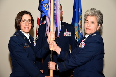U.S. Air Force Col. Janet Urbanski, 17th Medical Group commander, accepts the guideon from Col. Kari Stone, 17th Medical Operation Squadron commander, during the 17th MDOS Change of Command at the Event Center on Goodfellow Air Force Base, Texas, June 21, 2018. The guideon signifies the passing of command from one commander to the next. (U.S. Air Force photo by Airman 1st Class Seraiah Hines/Released)