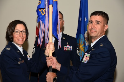 U.S. Air Force Col. Janet Urbanski, 17th Medical Group commander, passes the 17th Medical Operation Squadron guideon to Lt. Col. Shaun Westphal, 17th MDOS incoming commander, at the 17th MDOS Change of Command at the Event Center on Goodfellow Air Force Base, Texas, June 21, 2018. The change of command ceremony is a time honored military tradition that signifies the orderly transfer of authority. (U.S. Air Force photo by Airman 1st Class Seraiah Hines/Released)