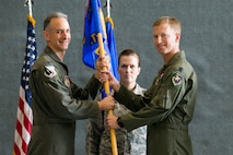 Col. Christopher Spinelli, 412th Operations Group Commander passes the 419th Flight Test Squadron guidon to Lt. Col. Thomas Meagher during a change of command ceremony June 15.