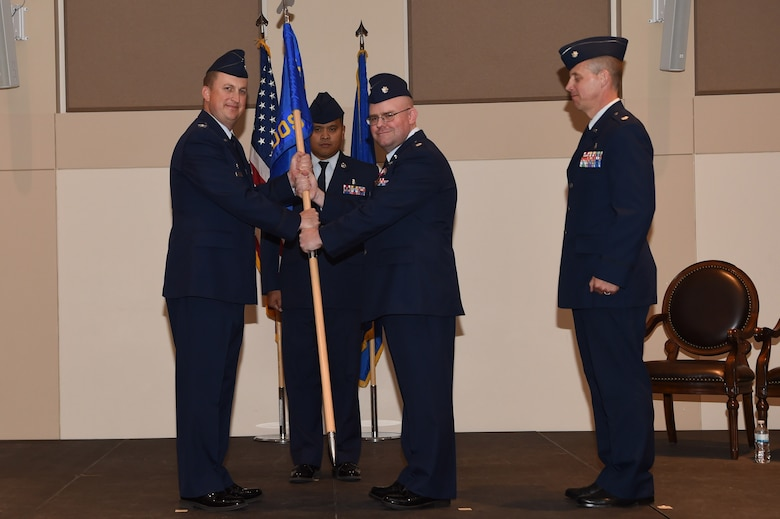Lt. Col. Jon O'Pry, center, 460th Medical Operations Squadron outgoing commander, pass the guidon to Col. Lorenzo Bradley, left, 460th Operation Group commander June 15, 2018, on Buckley Air Force Base, Colorado. The 460th MDOS mission is to provide medical and preventive health care to all wing and associated non-flying personnel and their dependents. (U.S. Air Force photo by Airman 1st Class Codie Collins)