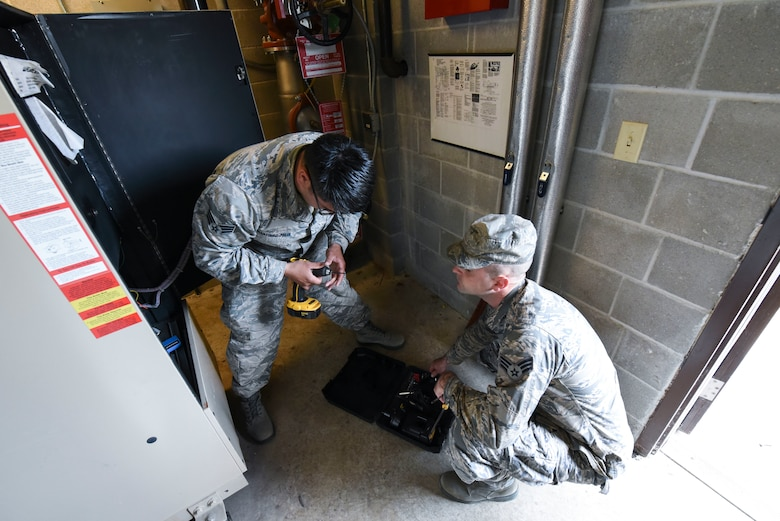 Senior Airman Kristian Martinez-felix, left, a 319th Civil Engineer Squadron heating, ventilation, air conditioning and refrigeration apprentice, and Senior Airman Tristan Miles, a 319th HVAC-R journeyman, maintain the water boilers June 20, 2018, on Grand Forks Air Force Base, North Dakota. Martinez-felix said that they typically work on the water boilers in the summertime to ensure they are prepared for the winter months. (U.S. Air Force photo by Airman 1st Class Melody Wolff)