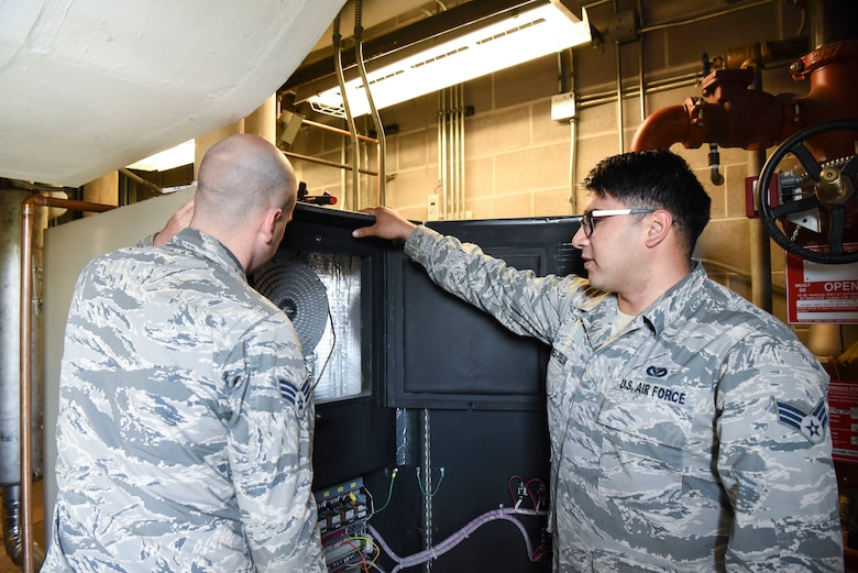 Senior Airman Kristian Martinez-felix, right, a 319th Civil Engineer Squadron heating, ventilation, air conditioning and refrigeration apprentice, and Senior Airman Tristan Miles, a 319th HVAC-R journeyman, begin maintenance on the water boilers June 20, 2018, on Grand Forks Air Force Base, North Dakota. Martinez-felix said that every building on base will have a water boiler in the building. (U.S. Air Force photo by Airman 1st Class Melody Wolff)