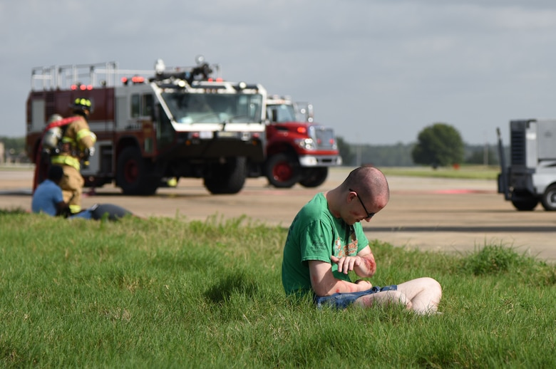 "U.S. Air Force Staff Sgt. Robert Herr, 333rd Training Squadron student, portrays a ""victim"" during a major accident response exercise on the flight line at Keesler Air Force Base, Mississippi, June 21, 2018. The exercise scenario simulated a C-130J Super Hercules in-flight emergency causing a plane crash, which resulted in a mass casualty response event. This exercise tested the base's ability to respond in a crisis situation. (U.S. Air Force photo by Kemberly Groue)"