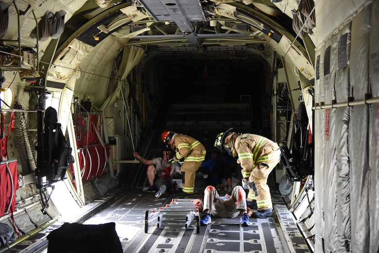 "A Keesler Firefighters retrieve ""victims"" from the inside of a C-130J Super Hercules during a major accident response exercise at Keesler Air Force Base, Mississippi, June 21, 2018. The exercise scenario simulated a C-130J Super Hercules in-flight emergency causing a plane crash which resulted in a mass casualty response event. This exercise tested the base's ability to respond in a crisis situation. (U.S. Air Force photo by Kemberly Groue)"