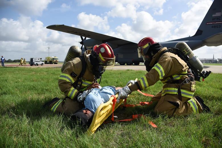 "Keesler Firefighters provide medical treatment to U.S. Air Force Airman Alex Gonzalez, 334th Training Squadron student, who portrays a ""victim"" during a major accident response exercise on the flight line at Keesler Air Force Base, Mississippi, June 21, 2018. The exercise scenario simulated a C-130J Super Hercules in-flight emergency causing a plane crash, which resulted in a mass casualty response event. This exercise tested the base's ability to respond in a crisis situation. (U.S. Air Force photo by Kemberly Groue)"