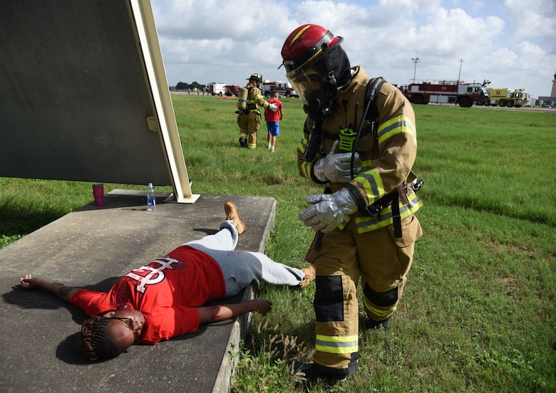"A Keesler Firefighter provides assistance to U.S. Air Force Tech. Sgt. Shanikqua Lucas, 81st Force Support Squadron manpower analyst, who portrays a ""victim"" during a major accident response exercise on the flight line at Keesler Air Force Base, Mississippi, June 21, 2018. The exercise scenario simulated a C-130J Super Hercules in-flight emergency causing a plane crash, which resulted in a mass casualty response event. This exercise tested the base's ability to respond in a crisis situation. (U.S. Air Force photo by Kemberly Groue)"