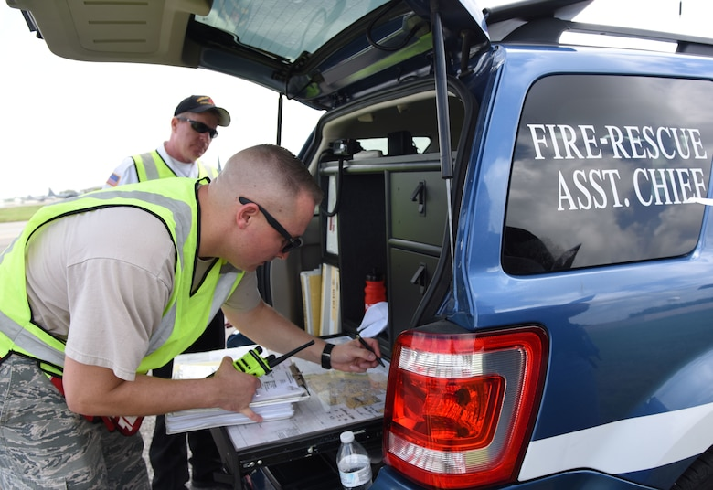U.S. Air Force Master Sgt. Dan Blankenship, 81st Infrastructure Division operations assistant chief and Gary Pierson, 81st ID deputy fire chief, document the number of victims at the crash site during a major accident response exercise on the flight line at Keesler Air Force Base, Mississippi, June 21, 2018. The exercise scenario simulated a C-130J Super Hercules in-flight emergency causing a plane crash which resulted in a mass casualty response event. This exercise tested the base's ability to respond in a crisis situation. (U.S. Air Force photo by Kemberly Groue)