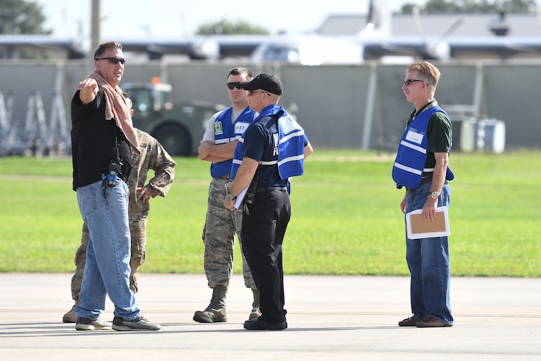 Members of the 81st Training Wing wing inspection team discuss the scenario during a major accident response exercise on the flight line at Keesler Air Force Base, Mississippi, June 21, 2018. The exercise scenario simulated a C-130J Super Hercules in-flight emergency causing a plane crash, which resulted in a mass casualty response event. This exercise tested the base's ability to respond in a crisis situation. (U.S. Air Force photo by Kemberly Groue)