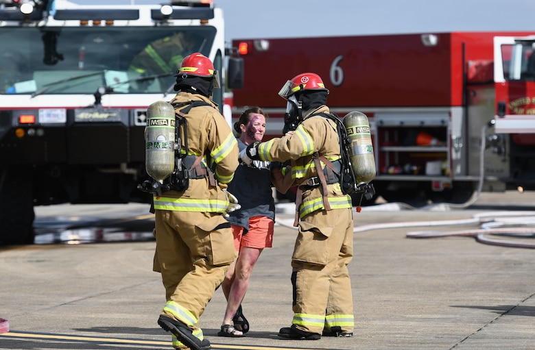 "Keesler Firefighters provide assistance to U.S. Air Force Master Sgt. Tiffany Satterwhite, 81st Training Wing inspector general superintendent, who portrays a ""victim"" during a major accident response exercise on the flight line at Keesler Air Force Base, Mississippi, June 21, 2018. The exercise scenario simulated a C-130J Super Hercules in-flight emergency causing a plane crash, which resulted in a mass casualty response event. This exercise tested the base's ability to respond in a crisis situation. (U.S. Air Force photo by Kemberly Groue)"