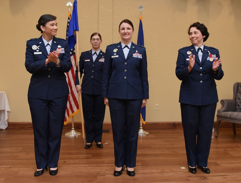 U.S. Air Force Col. Debra Lovette, 81st Training Wing commander, and Col. Jeannine Ryder, outgoing 81st Medical Group commander, congratulate Col. Beatrice Dolihite, incoming 81st MDG commander, during the 81st MDG change of command ceremony in the Bay Breeze Event Center at Keesler Air Force Base, Mississippi, June 22, 2018. The passing of the guidon is a ceremonial symbol of exchanging command from one commander to another. (U.S. Air Force photo by Kemberly Groue)