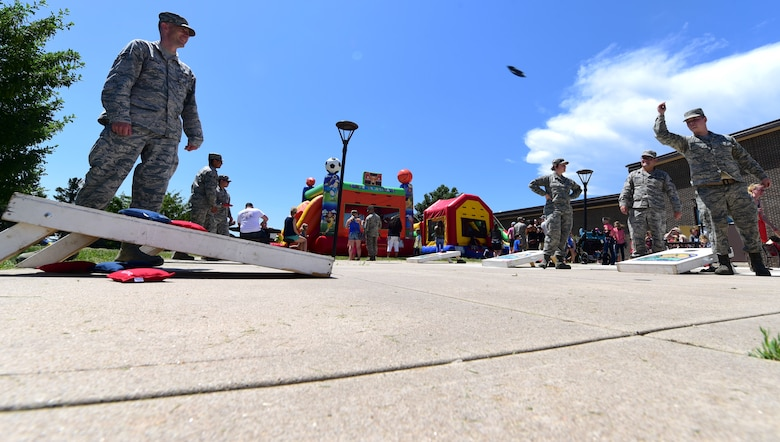 Airmen participate in a game of cornhole during the annual base picnic outside the Dakota's Club at Ellsworth Air Force Base, S.D., June 22, 2018. The purpose of the base picnic was to thank the members of Ellsworth for their hard work, as well as celebrate the start of summer. (U.S. Air Force photo by Senior Airman Randahl Jenson)